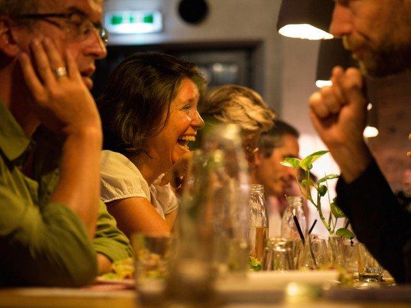 Mucbook: Rückblick auf das erste Erzähl-Mahl in München, lachende Frau am Tisch