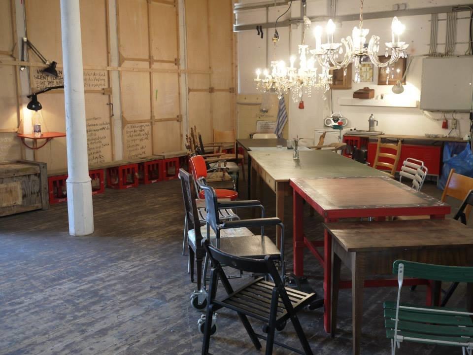 Mucbook: Laborküche im Kreativquartier mit geretteten Lebensmitteln am 31.10., Dinnertafel aus bunt zusammengewürfelten Tischen und Stühlen