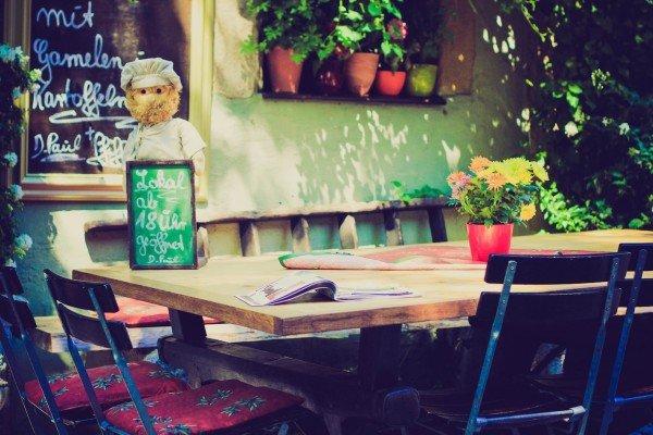 Mucbook: Erzähl-Mahl. Holztisch mit Stühlen vor einem Lokal