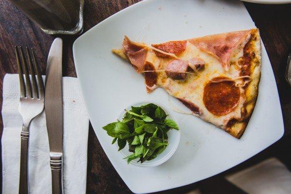 Restaurant Day am 21.11.: PizzaPazza meets Abendesser Connection. Stück Pizza mit Schinken und Salami auf einem Teller