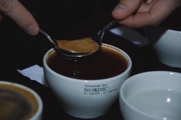Mucbook: Cupping im Münchner Mahlefitz. Tasse Kaffee, Schaum wird mit Löffeln abgeschöpft