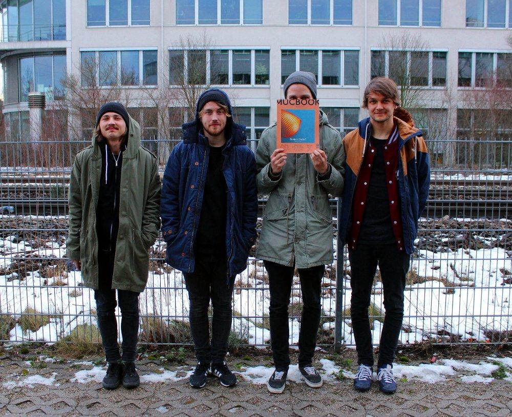 v.l.n.r.: Moritz (Gitarre), Mario (Gesang, Gitarre), Michael (Schlagzeug) mit Mucbook Print, Marcus (Bass, Gesang)