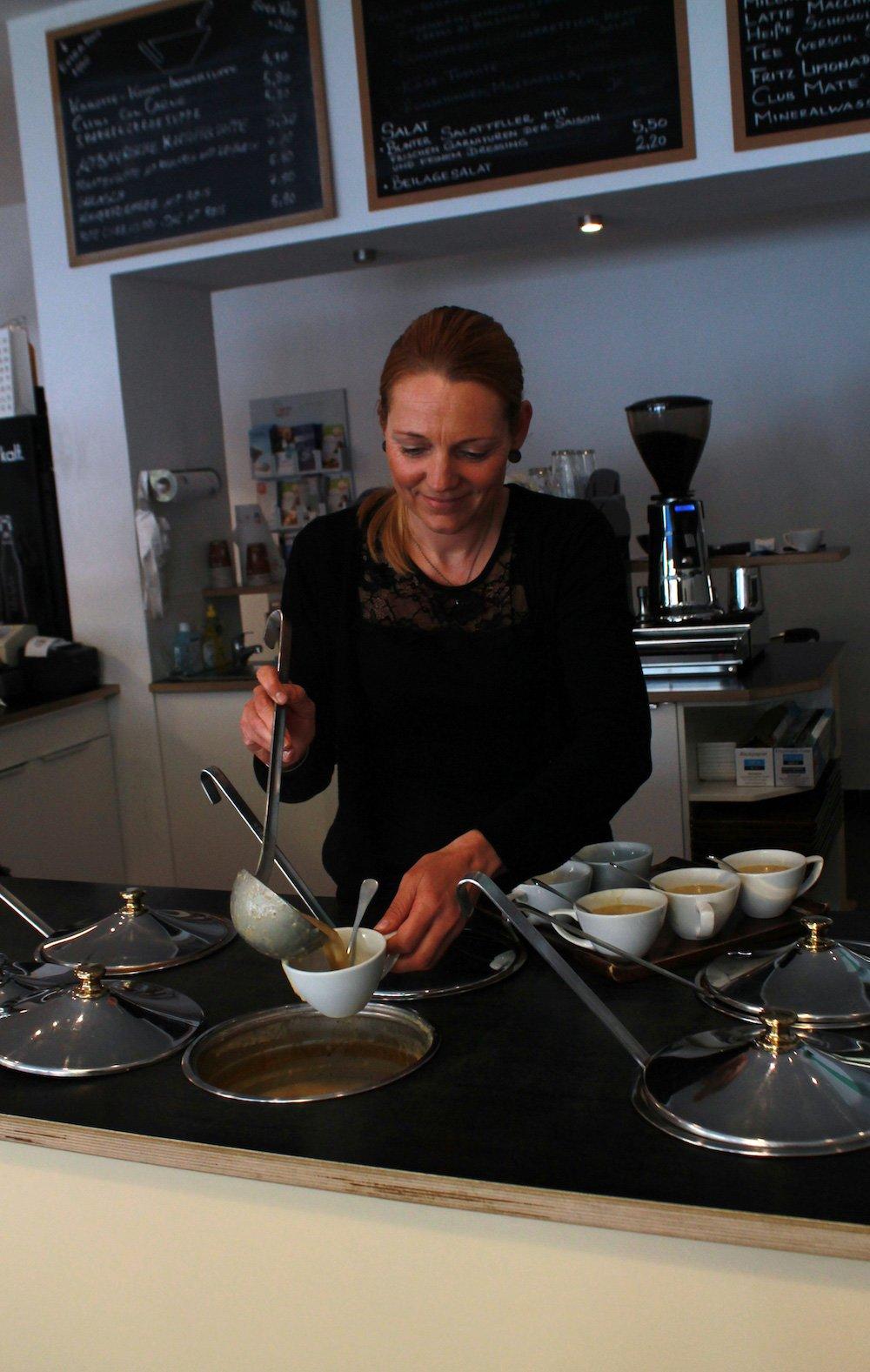 Mucbook: Gusto - leckere Suppenküche in München-Neuhausen. Weibliche Bedienung schöpft Suppe in eine Schale