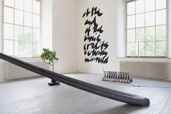 Kunstwerk mit Baum, Wandschrift und Stoffbahnen, gefüllt mit Steinen.