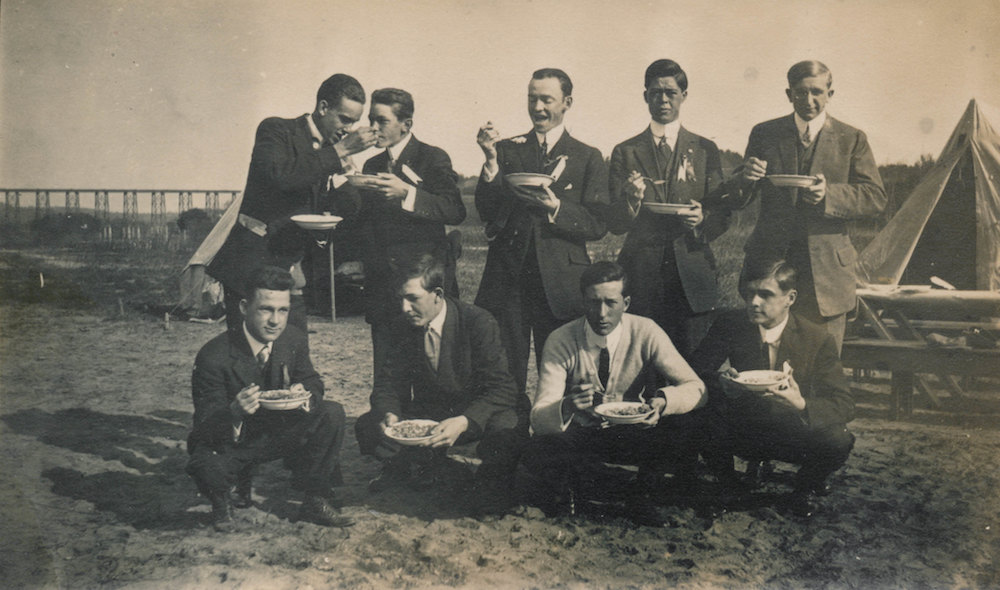 Group of men eating and feeding each other